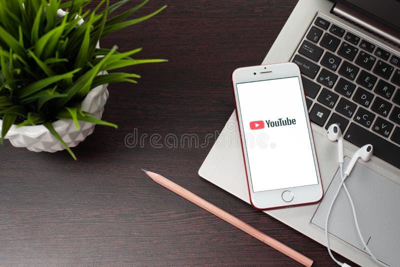 Деятельность применения Youtube на iPhone 7 Яблока с белым наушником стоковые фотографии rf