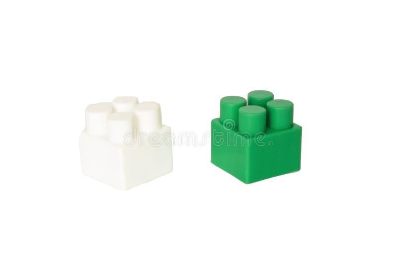детали children& x27; конструктор s пластиковый на белой предпосылке Покрашенные кубики засорением стоковое фото