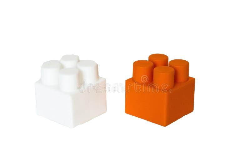 детали children& x27; конструктор s пластиковый на белой предпосылке Покрашенные кубики засорением стоковое фото rf