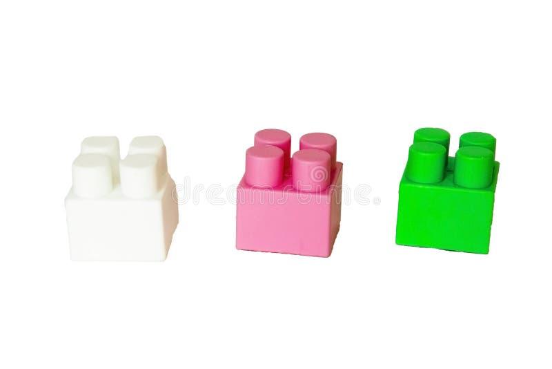 детали children& x27; конструктор s пластиковый на белой предпосылке Покрашенные кубики засорением стоковая фотография