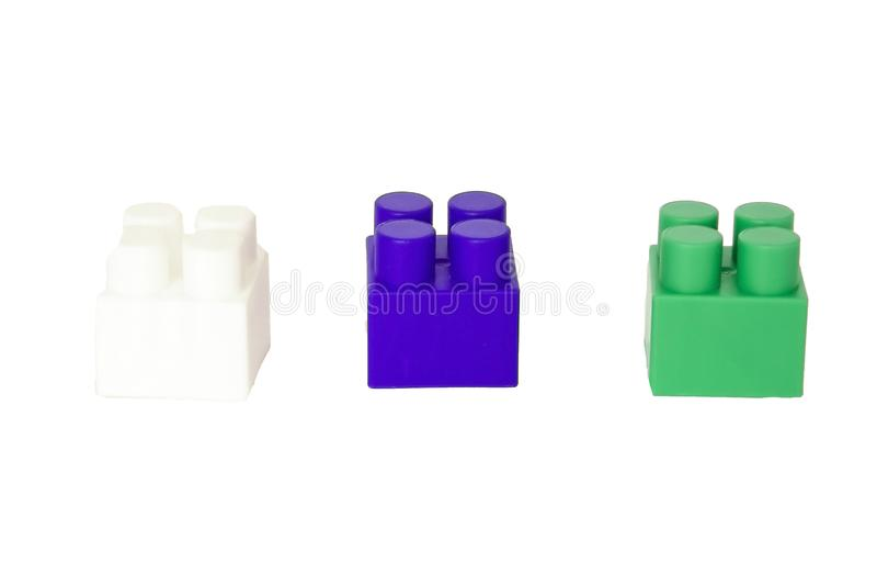 детали children& x27; конструктор s пластиковый на белой предпосылке Покрашенные кубики засорением стоковая фотография rf