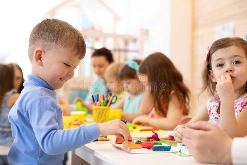 Дети играя с красочной глиной на детском саде стоковое изображение