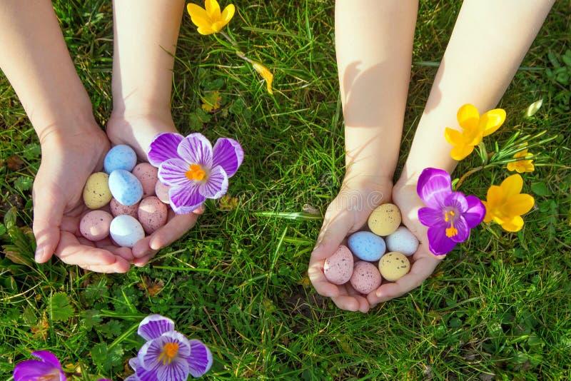 Дети ищут и находят пасхальные яйца Концепция праздников пасхи стоковая фотография