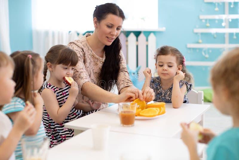 Дети и человек осуществляющий уход совместно едят плоды в детском саде или daycare стоковая фотография