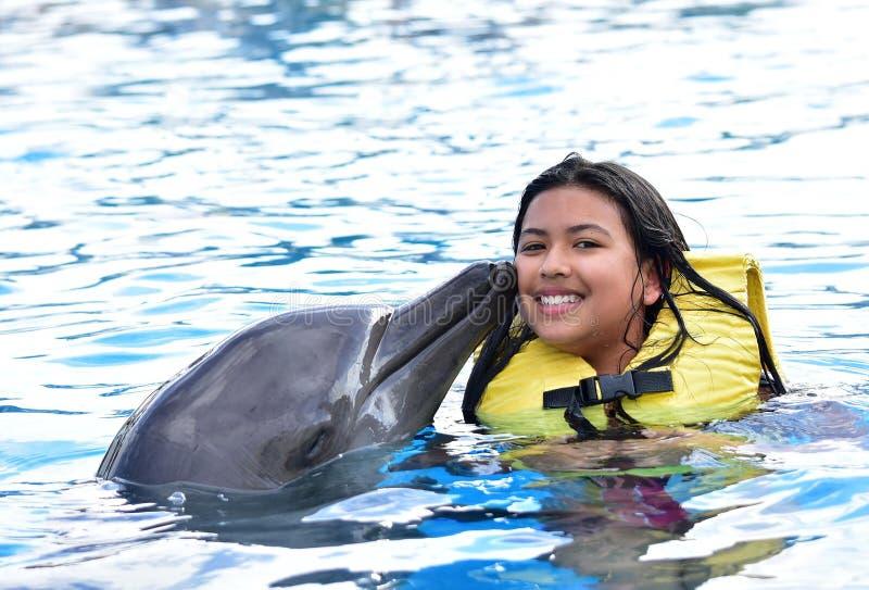 Дети целуя дельфина в бассейне стоковая фотография