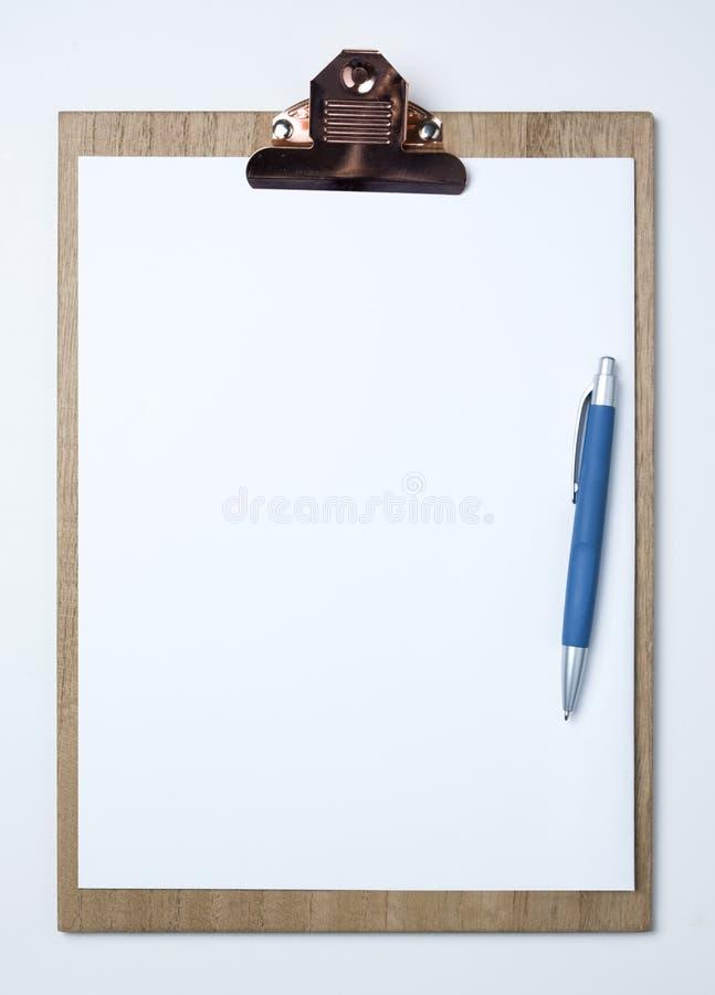 Деревянная доска сзажимом для бумаги с белым листом дальше стоковые фото
