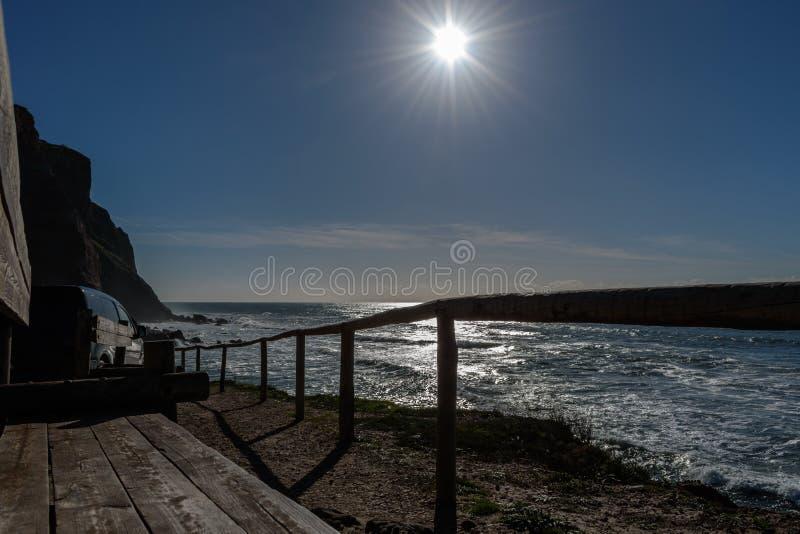 Деревянные скамьи и загородка с автомобилем припаркованным рядом со скалой на пляже Порту Barril с ярким солнцем, Ericeira - Mafr стоковые фото