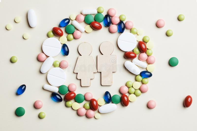 Деревянные человек и женщина игрушки в красочных таблетках, капсулах и планшетах медицины объезжают стоковое изображение