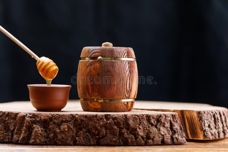 Деревянный бочонок с медом и ложкой меда на деревянной пиле на темной предпосылке barrette стоковые фото