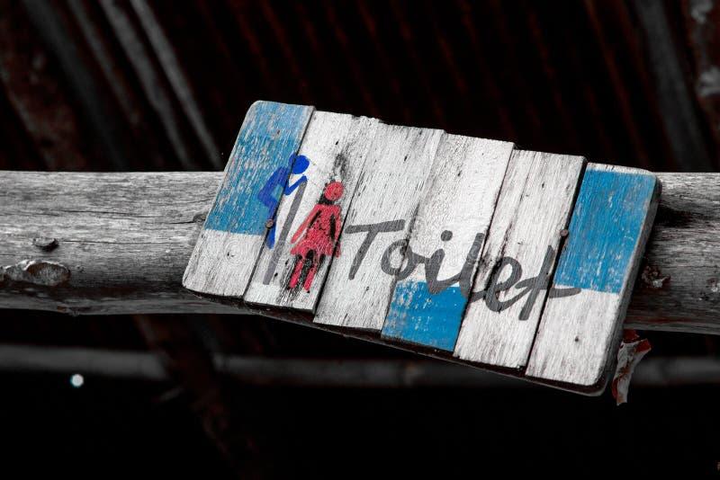 Деревянный знак туалета вися на деревянном поляке стоковые изображения