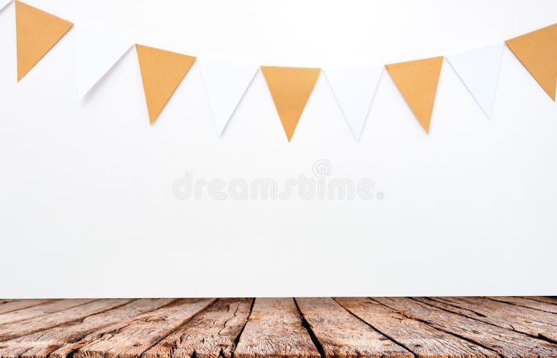 Деревянный стол и вися бумажные флаги на белой предпосылке стены, детали оформления для партии, фестиваля, празднуют событие стоковое фото rf