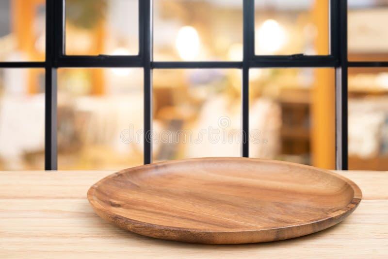 Деревянный стол перспективы и деревянный поднос на верхней части над предпосылкой кофейни нерезкости, могут быть используемое нас стоковые фото