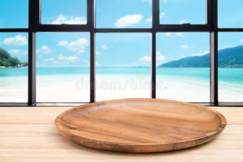 Деревянный стол перспективы и деревянный поднос на верхней части над предпосылкой вида на море нерезкости, могут быть используемо стоковое изображение rf
