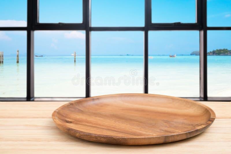 Деревянный стол перспективы и деревянный поднос на верхней части над предпосылкой вида на море нерезкости, могут быть используемо стоковое фото