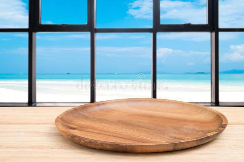 Деревянный стол перспективы и деревянный поднос на верхней части над предпосылкой вида на море нерезкости, могут быть используемо стоковые фотографии rf