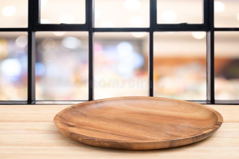 Деревянный стол перспективы и деревянный поднос на верхней части над предпосылкой света bokeh нерезкости, могут быть используемое стоковая фотография rf