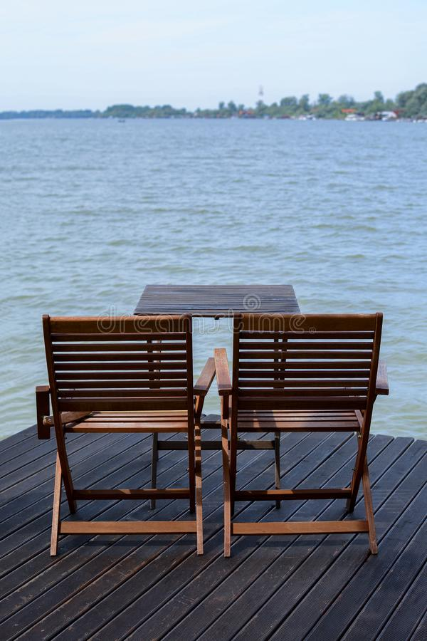 2 деревянных стуль на доке около воды стоковое фото