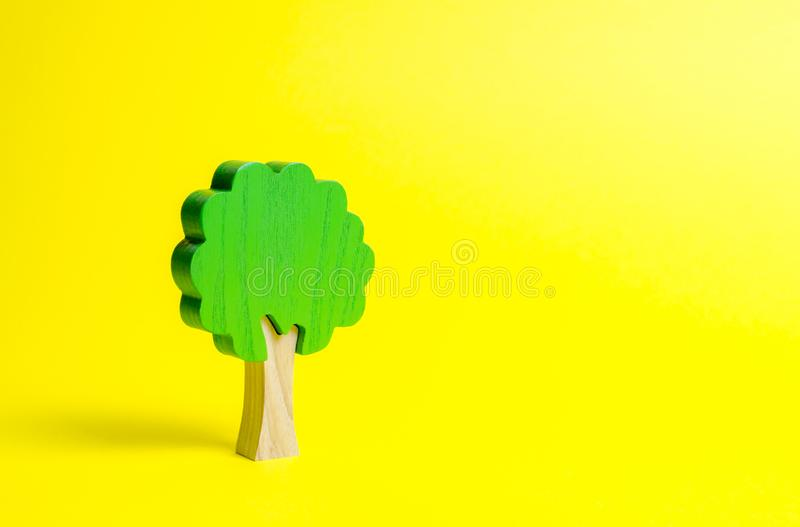 Дерево игрушки деревянное на желтой предпосылке Минимализм и концепция экологической консервации легкие планеты Семья стоковое фото
