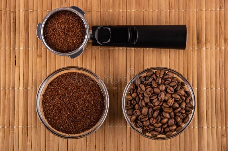 Держатель от кофеварки с кофе, шаром с зажаренными кофейными зернами, шаром с земным кофе на циновке Взгляд сверху стоковое фото rf