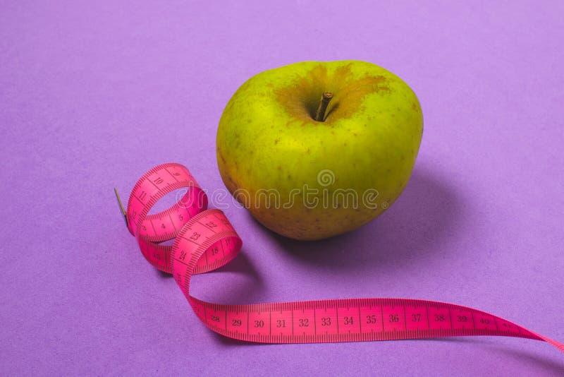 Диета, концепция потери веса минимальная, здоровая - зеленое яблоко, розовая измеряя лента, взгляд сверху, космос экземпляра, пур стоковая фотография rf