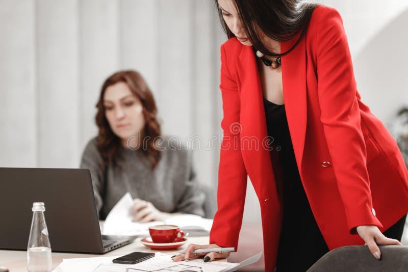 Дизайнер 2 молодых женщин работает на дизайн-проекте интерьера на столе с ноутбуком и документации в стоковые изображения