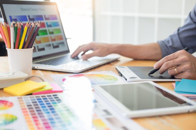 Дизайнер по интерьеру команды рисуя новый проект используя графический компьютер и выбирая образцы образца цвета в современной тв стоковые изображения