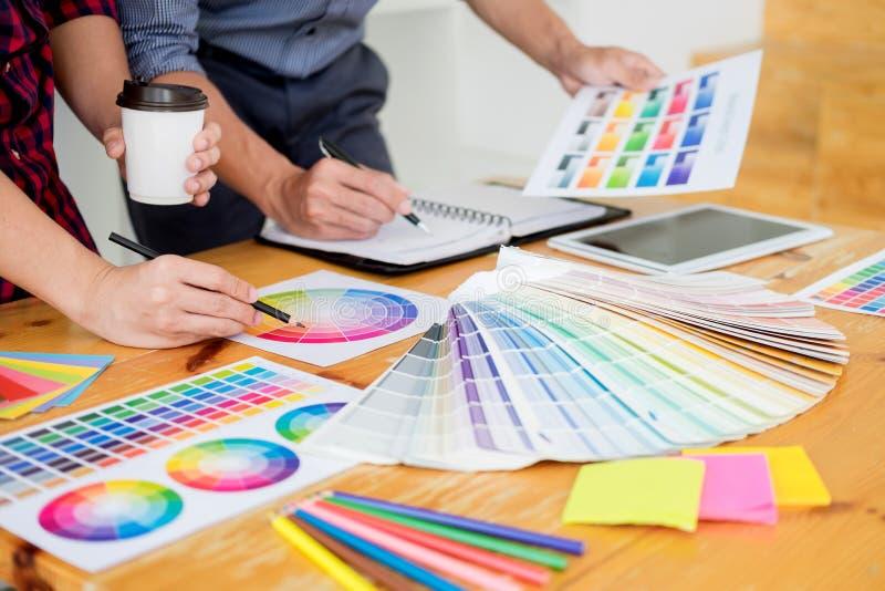 Дизайнер по интерьеру команды рисуя новый проект используя графический компьютер и выбирая образцы образца цвета в современной тв стоковые фото