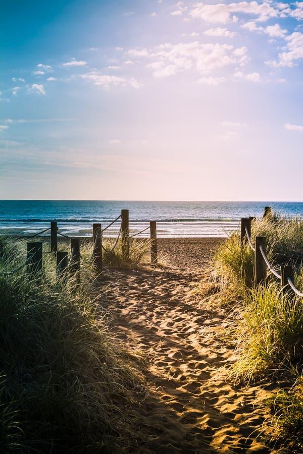 Длинные выравниваясь тени над песочной тропой с тростниками травы и деревянными столбами на каждой стороне водя к красивому залив стоковые изображения