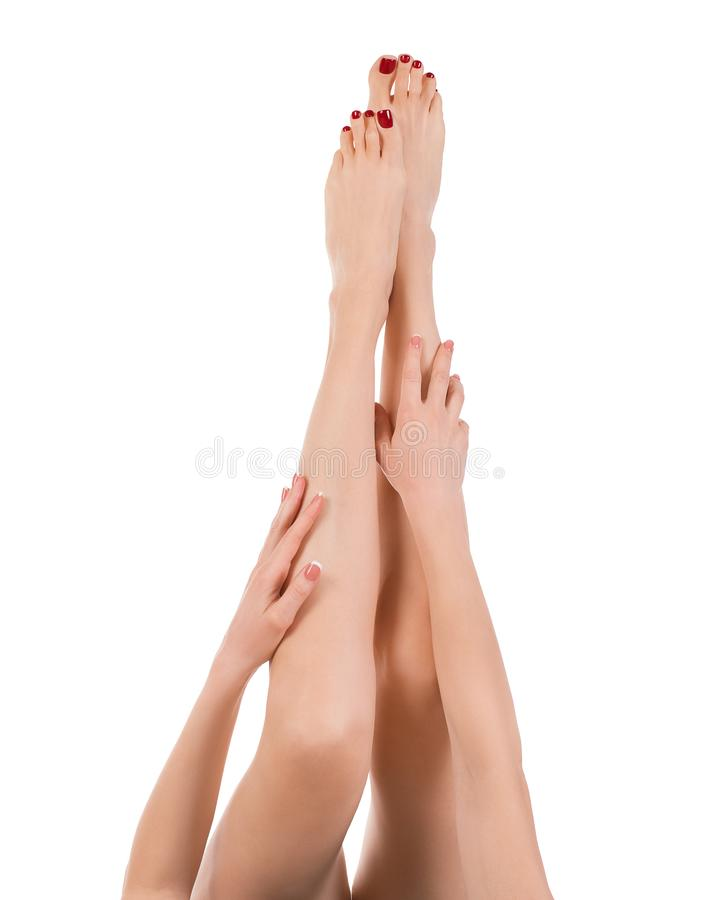 Длинные женские босоногие ноги поднимают вверх, классический красный pedicure, изолированный на белизне Хорошо выхоленная кожа стоковые изображения