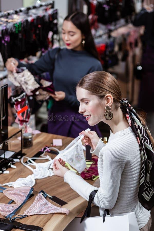 Длинн-с волосами молодая милая дама в белом свитере смотря позабавленный стоковая фотография