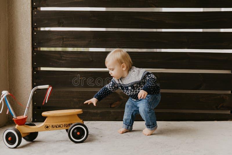Драгоценный прелестный милый маленький белокурый ребенк мальчика малыша младенца играя снаружи на деревянной черни скутера велоси стоковое фото rf