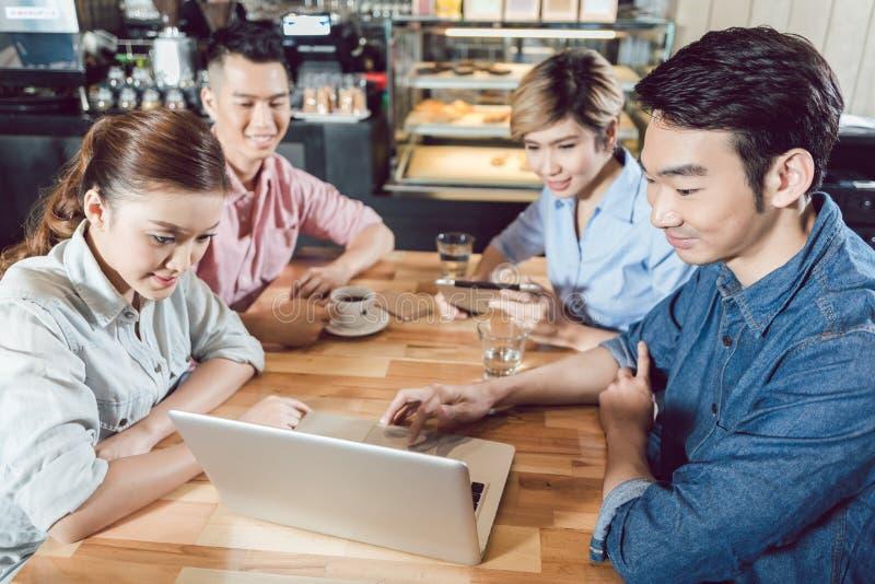 Друзья в кафе используя ноутбук стоковые фотографии rf