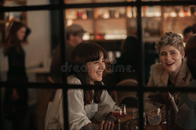 Друзья говоря над напитками на таблице бара в вечере стоковые изображения