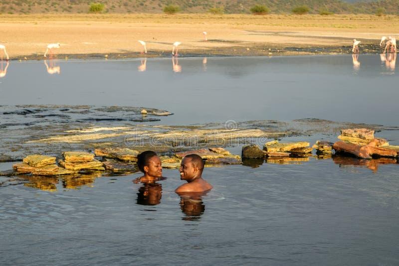 Друзья имея потеху на горячих источниках Magadi озера стоковые фото