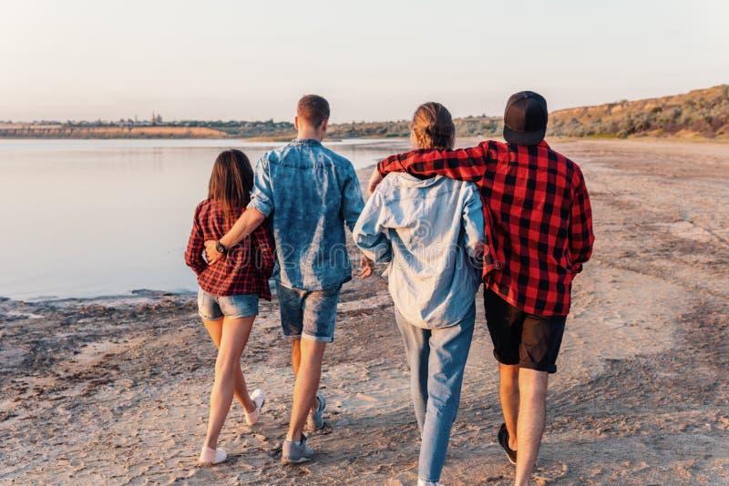 Друзья на пляже совместно идя во время захода солнца стоковое изображение rf