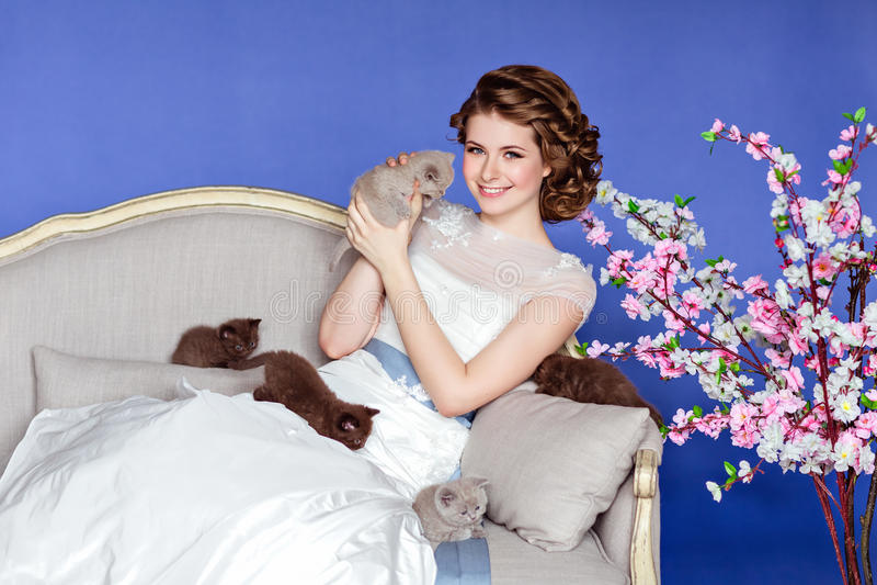 Ð ¡危害和白色礼服的美丽的女孩坐沙发  库存照片