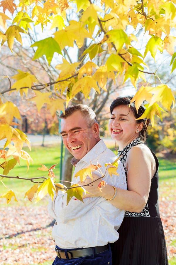 з美丽的走在公园的夫妇女孩和人在秋天天 库存图片