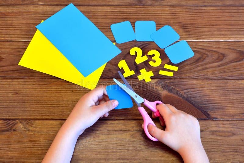 Ð-¡ hild rymmer saxen och klipper det pappers- kortet pappersdiagram arkivfoto