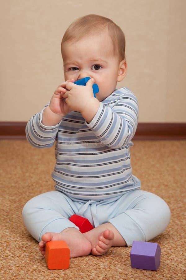 Ð ¡ hild siedzi na podłoga i ogryza zabawkę obrazy stock