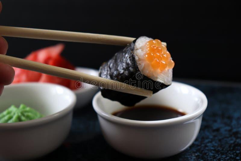Ð-iece von Sushi mit Kaviar Sushi gegessen mit Essstäbchen stockbild