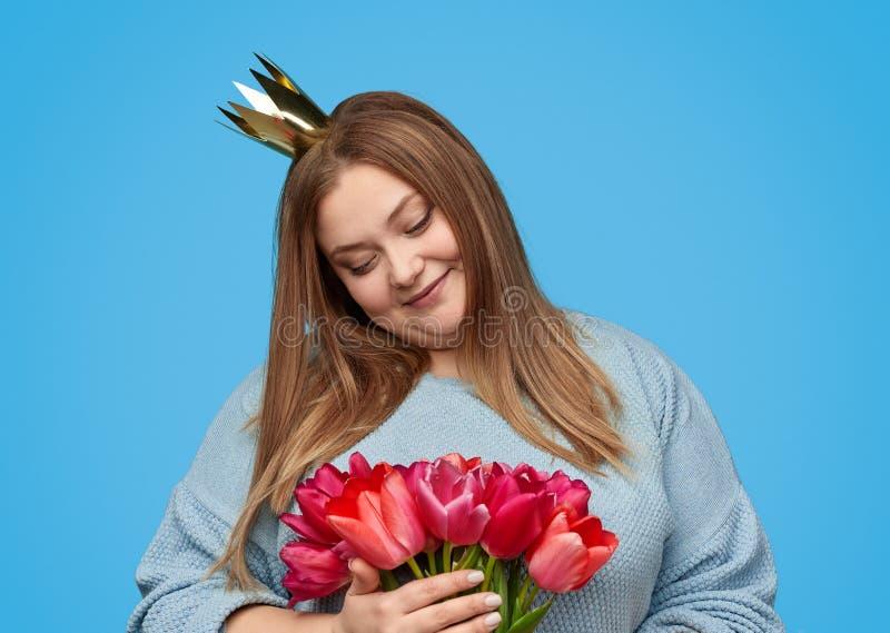Добавочная женщина размера смотря красные цветки стоковая фотография