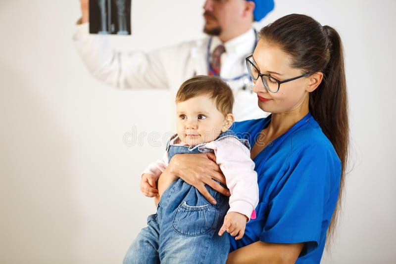 Довольныйся ребенок в оружиях доктора, на заднем плане доктор смотрит рентгеновский снимок Белая предпосылка стоковое изображение