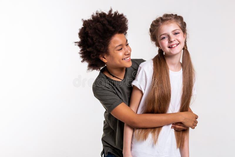 Довольный Афро-американский мальчик плотно хватая его маленького друга стоковое изображение rf
