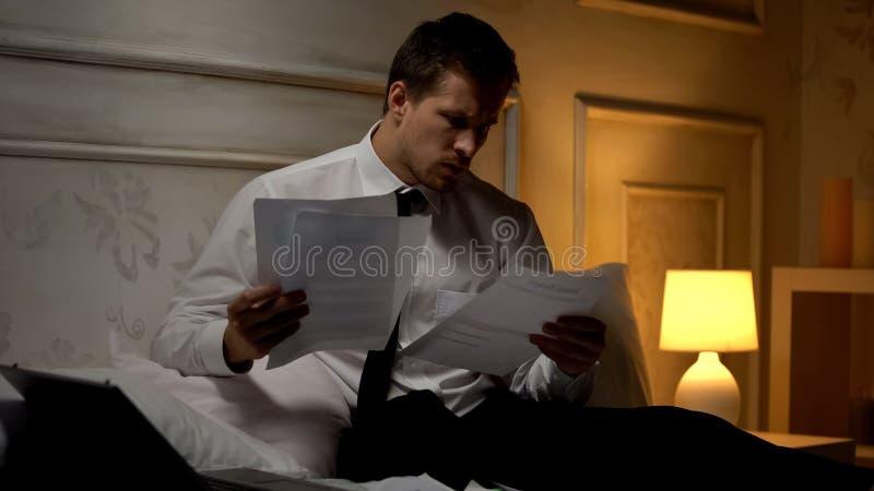 Документы чтения работодателя дома, удаленная работа, недостаток сна стоковое изображение