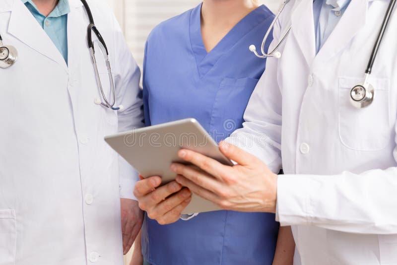 Доктор и медицинская бригада обсуждая терпеливый отчет на планшете в больнице стоковое фото