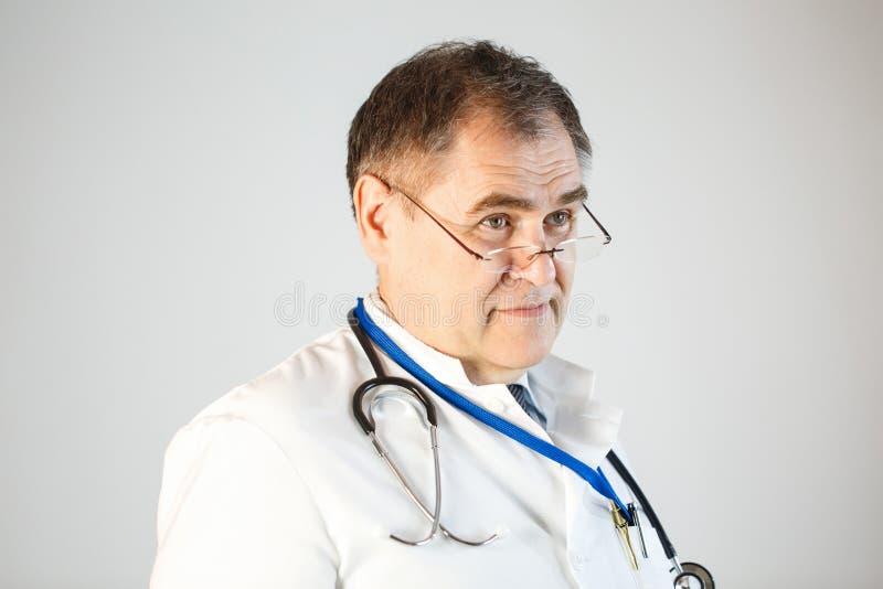 Доктор смотрит вперед, стекла на подсказке его носа, брови поднял, стетоскоп и значок вися от его шеи стоковое фото