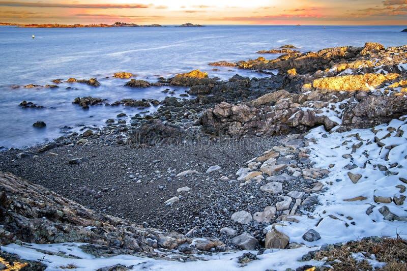 Долгая выдержка снежного и скалистый обозревает океана и побережья во время зимы стоковые фото