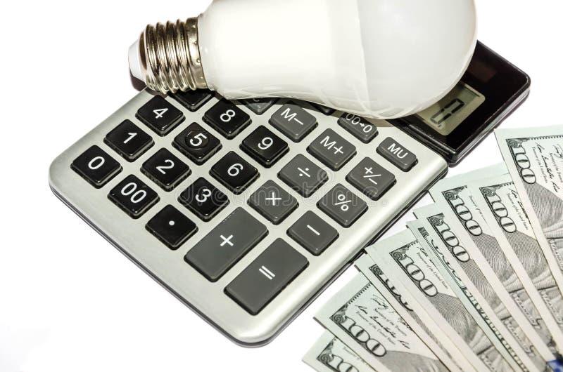 Доллары, электрическая лампочка и калькулятор изолированные на белизне стоковое фото rf