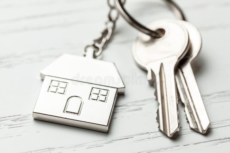 Дом и ключи Keychain на белой деревянной предпосылке стоковое изображение