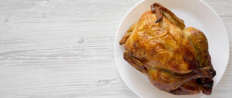 Домодельный вкусный цыпленок rotisserie на белой плите над белой деревянной предпосылкой, взглядом сверху скопируйте космос стоковое изображение